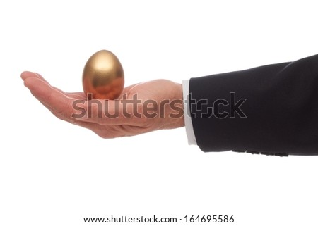 A Golden Egg Resting in the Palm of a Hand - stock photo