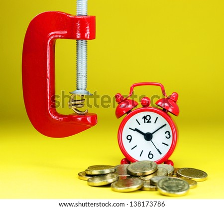 A golden Euro symbol placed in a red clamp with a yellow background, with a red alarm clock in the background, with some golden coins indicating the pressure on pound. - stock photo