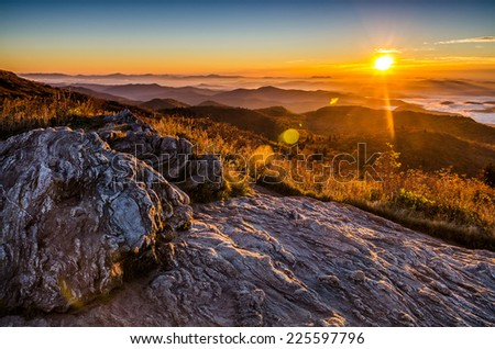 A golden fall sunrise over the Blue Ridge Mountains from atop Black Balsam Bald in North Carolina. - stock photo