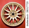 a golden hubcap isolated over red background - stock photo