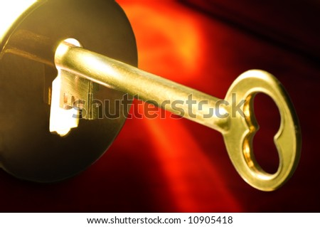 A golden key in a keyhole illuminated by a mysterious radiant light from the other side on red background.