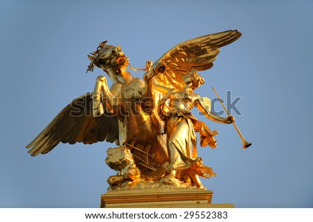 A golden mythological statue of winged horse and woman. - stock photo
