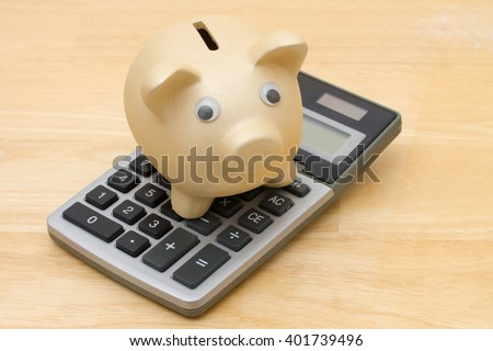 A golden piggy bank and calculator on a wood background
