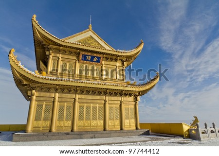 A golden temple at the top of the hill with blue sky - stock photo