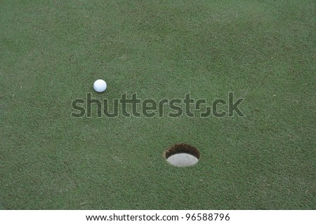 A golf ball near the hole on a green - stock photo