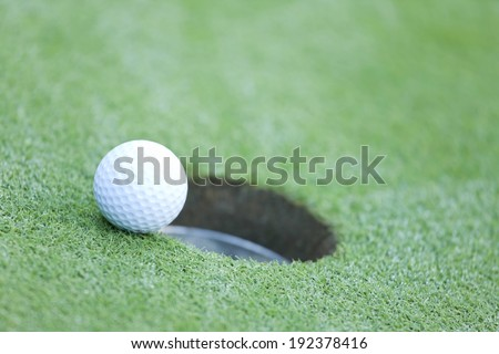 A golf ball on the brink of falling into the hole. - stock photo