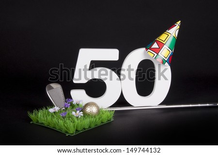 A golf club and golf ball on an artificial peace of grass to be used as a birthday card - stock photo