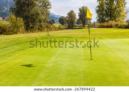 a golf hole with a flag pole in a beautiful golf course - stock photo
