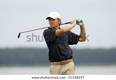 A golf player strikes a good shot - stock photo