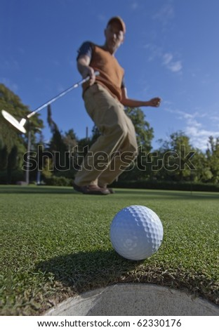 A golfball just as it's about to drop into the cup, golfer in the background arching as it drops - stock photo