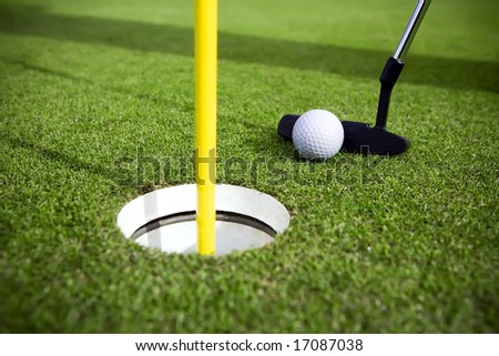 A golfer attempts to make a short putt - stock photo