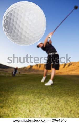 A golfer driving the ball down the fairway focus on the ball - stock photo