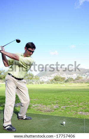 A golfer in action on a practice range, hitting the ball with a club. - stock photo