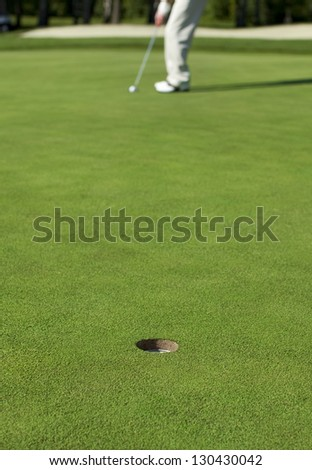 A golfer lines up a putt on a green. Focus on the hole. - stock photo