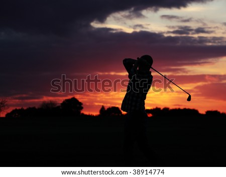 A golfer making the most of the remaining light and playing on - stock photo