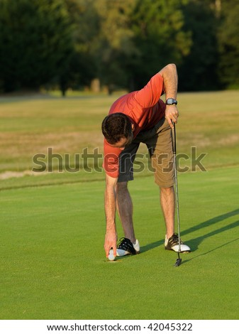 A golfer picking up his ball. - stock photo