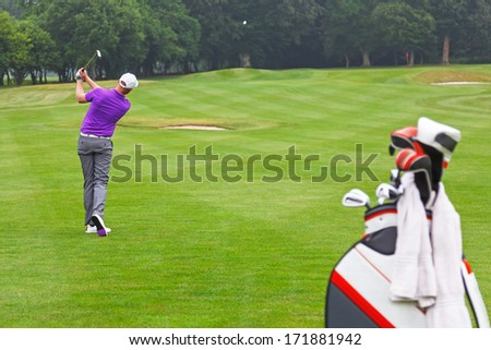 A golfer playing a mid iron fairway shot into the green on a par 4 hole, series of 3. Focus is on the golfer. - stock photo