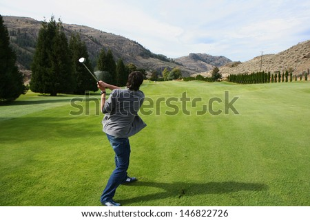 A golfer playing golf in the green field. - stock photo