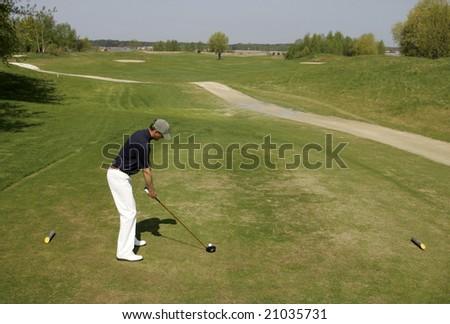 A golfer strikes a golf tee shot - stock photo