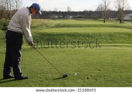 A golfer strikes a tee shot - stock photo