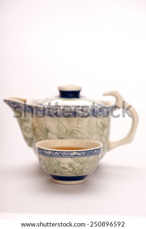 A good cup of tea. Closeup image of traditional crockery set isolated on white background with selective focus on teacup  - stock photo