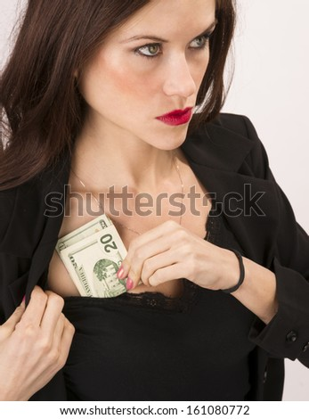 A good looking brunette woman stuffs cash money into her shirt business jacket - stock photo