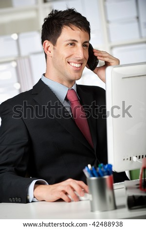 A good looking businessman talking on the phone while using a computer at the office