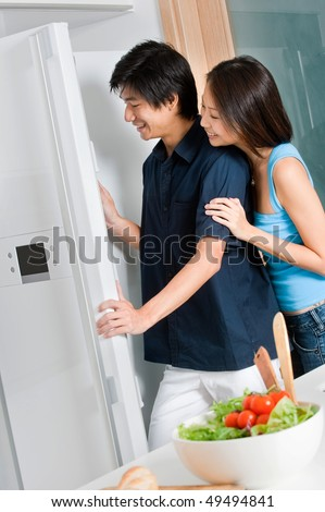 A good looking couple looking in their refrigerator while preparing a salad in their kitchen - stock photo