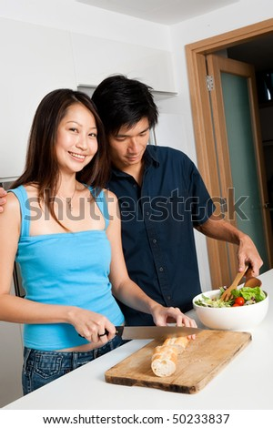 A good looking couple preparing a meal of bread and salad in the kitchen at home - stock photo