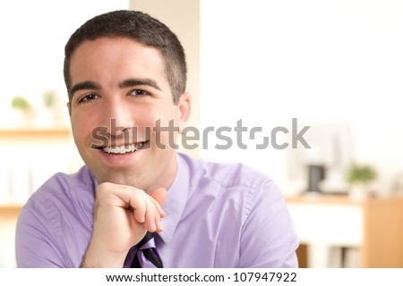 A good looking guy at work with a big smile on his face leaning his chin on his hand with dark hair and brown eyes. - stock photo
