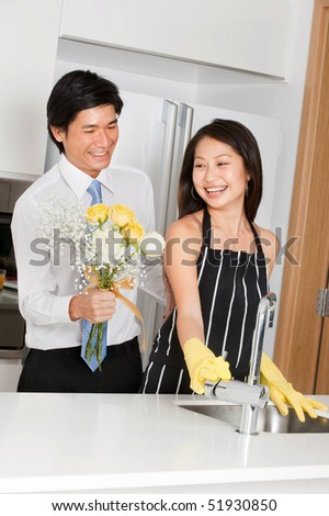 A good looking man giving a bouquet of flowers to his wife at home - stock photo