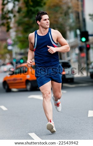 A good-looking man is out running in the city - stock photo