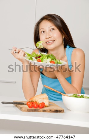 A good looking woman eating a healthy meal of bread and salad in her kitchen - stock photo