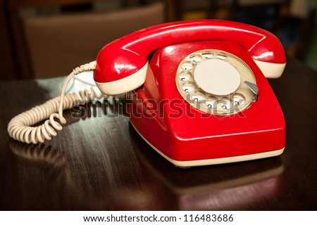 A good old fashioned red telephone, over a wooden table, makes people remember the 70`s or 80`s - stock photo