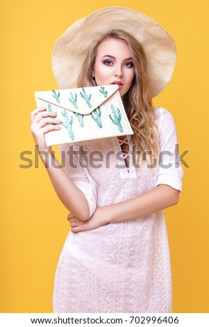 A gorgeous blonde girl in a white thin tunic, a big hat and with a clutch in her hands posing in the studio on a yellow background.