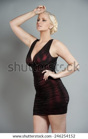 A gorgeous busty blonde with blue eyes wearing a red tight dress with her hair down on a gray background in a studio. - stock photo