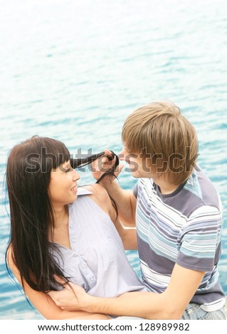 A gorgeous couple roaming at the sea shore - stock photo