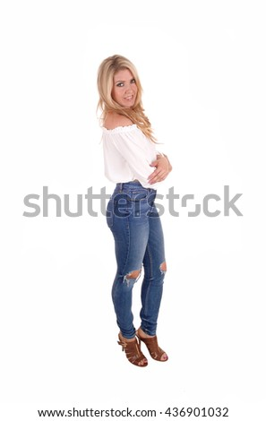 A gorgeous young blond woman standing in jeans and white blouse inprofile isolated for white background. - stock photo