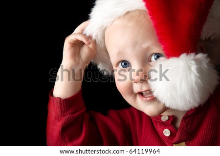 A gorgeous young boy peeking out from behind a santa hat. - stock photo