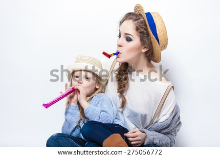 A gorgeous young mother blowing on a party favor while hugging daughter - stock photo