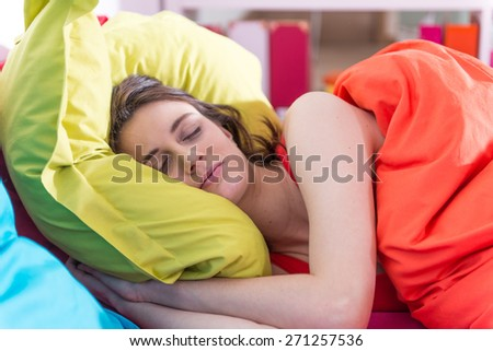 a gorgeous young woman sleeps in bed,  colored pillow in her arms,bedding is bright color, her sunny apartment is modern and bright - stock photo