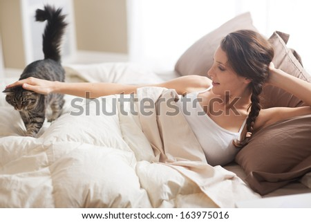 A gorgeous young woman while lying in bed with a cat - stock photo