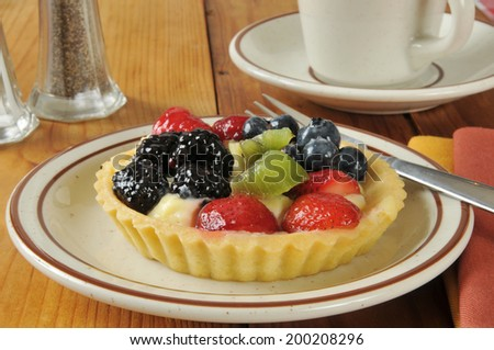 A gourmet fruit tart on a rustic wooden table with a cup of coffee
