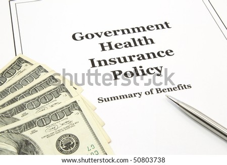 A government health insurance policy surround by hundred dollars bills and a pen.
