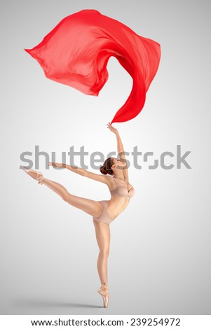 A graceful female classical ballet dancer on pointe shoes wearing beige underwear, standing on one leg in arabesque position and throwing red fabric on a neutral light studio background. - stock photo