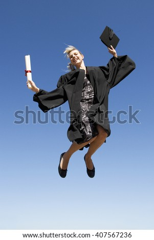 A graduate jumping for joy - stock photo