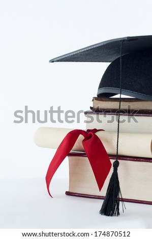 A graduation mortarboard on top of a stack of books, with parchment scroll tied in red ribbon. - stock photo