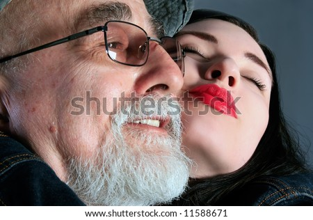 a granddaughter is hugging her grandpa - stock photo