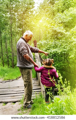 A grandfather with his granddaughter showing her something  in woods.  - stock photo