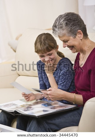 A grandmother looking through a photo album with her granddaughter.  They are both smiling.  Vertically framed shot. - stock photo